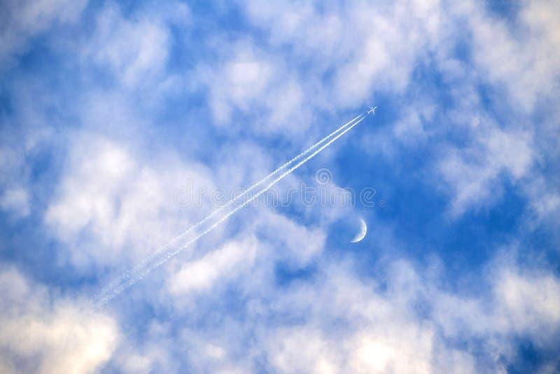 Vliegtuig die door wolken met maan vliegen royalty-vrije stock fotografie