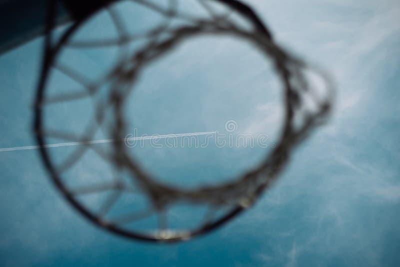 Vliegtuig die in duidelijke blauwe hemel met sommige nevel witte wolken vliegen die lange sleep over de hoepel van het Basketbalh royalty-vrije stock afbeelding