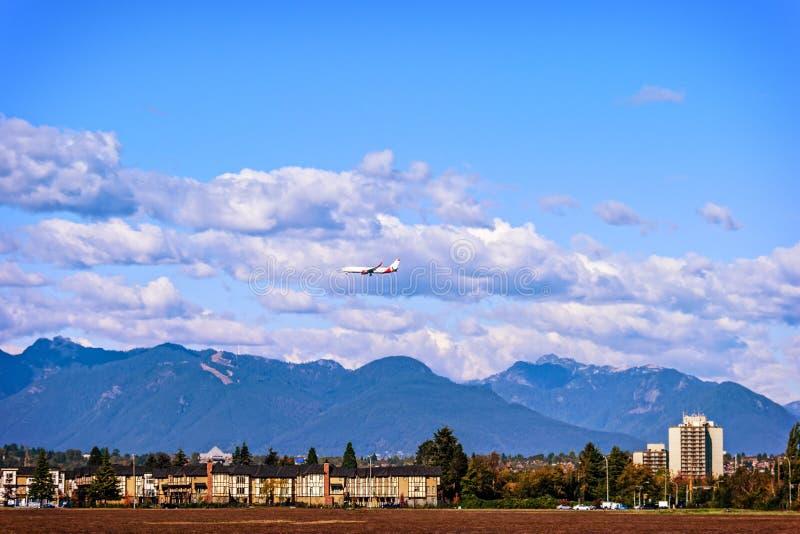 Vliegtuig die onder de wolken over de gebouwen vliegen royalty-vrije stock fotografie