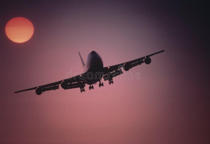 Vliegtuig die onder het plaatsen zon bij Zonsondergang vliegen royalty-vrije stock afbeelding