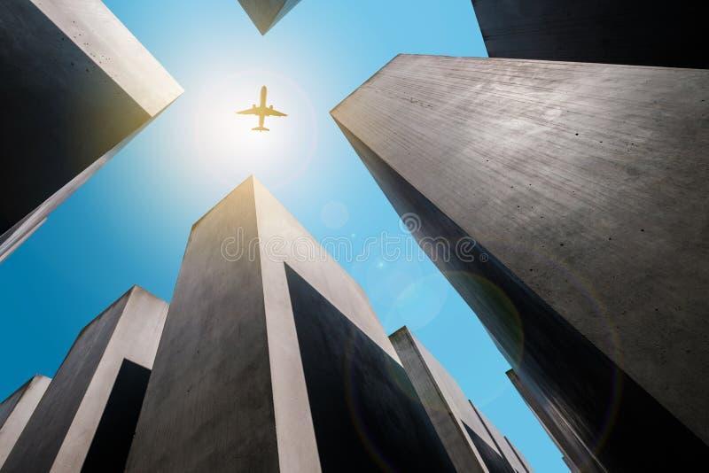 Vliegtuig die over Gedenkteken aan de moorde Joden vliegen/het Holocaustgedenkteken in Berlijn stock foto