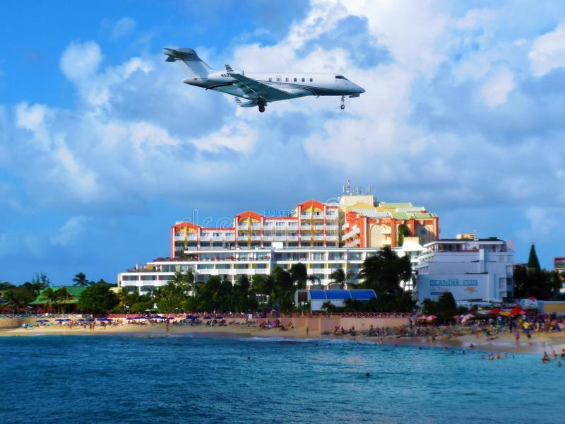 Vliegtuig die over Maho Beach bij St Maarten vliegen stock afbeelding