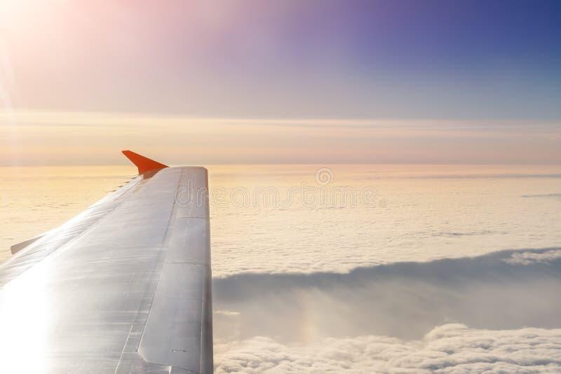 Vliegtuig die over wolken bij dageraad vliegen Vliegtuigvleugel over mooie cloudscape tijdens dramatische kleurrijke zonsondergan royalty-vrije stock foto's