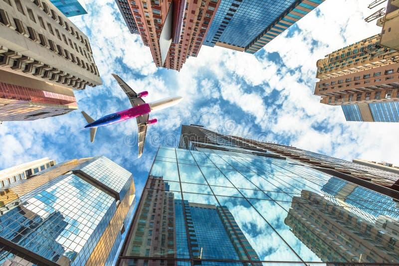 Vliegtuig die over wolkenkrabbers vliegen royalty-vrije stock foto's