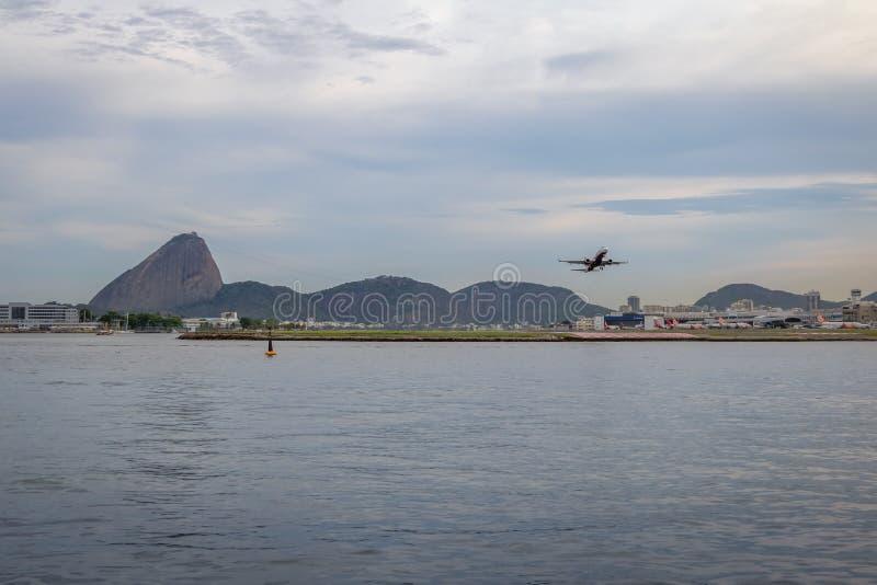 Vliegtuig die in Rio de Janeiro Airport met Sugar Loaf op achtergrond van start gaan - Rio de Janeiro, Brazilië stock foto's