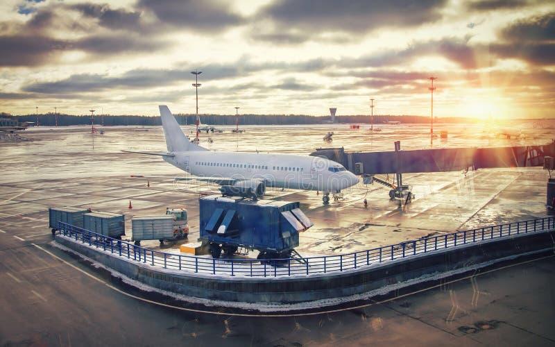 Vliegtuig in luchthaventerminal bij zonsondergang Het de dienstwerk van het controleren van vliegtuigen vóór start Het inschepen  stock foto