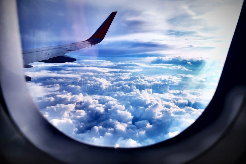 Vliegtuig, mening van de patrijspoort op de vleugel, wolken, zon stock afbeeldingen