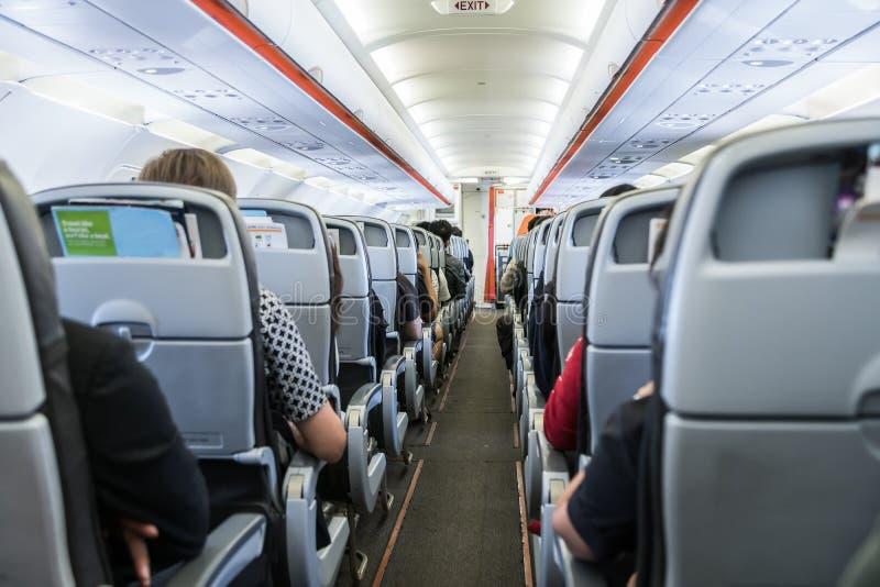 Vliegtuig met passagiers op zetels die wachten op te stijgen stock foto's