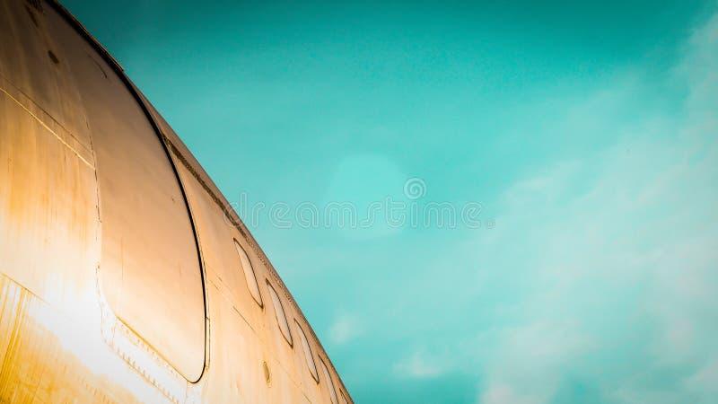 Vliegtuig op luchthavenbaan wordt geparkeerd op blauwe hemelachtergrond die wordt geïsoleerd stock foto