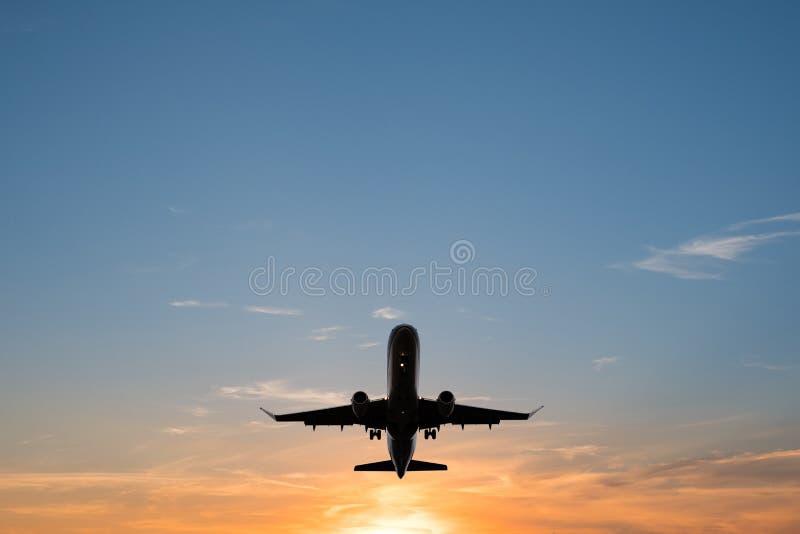 Vliegtuig op zonsonderganghemel, de toneelhemel van het vliegtuigensilhouet stock foto's