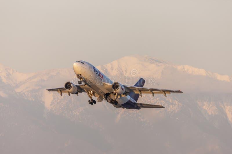 Vliegtuigen die van de de Luchtbusa310 lading van Fedex de Federale Uitdrukkelijke voor sneeuw afgedekte bergen opstijgen royalty-vrije stock foto's
