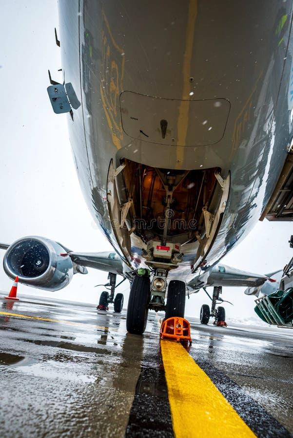 Vliegtuigen, neus dichte omhooggaand Vliegtuigonderhoud en vliegtuigvoorbereiding voor vertrek Slecht weer bij luchthaven royalty-vrije stock afbeelding