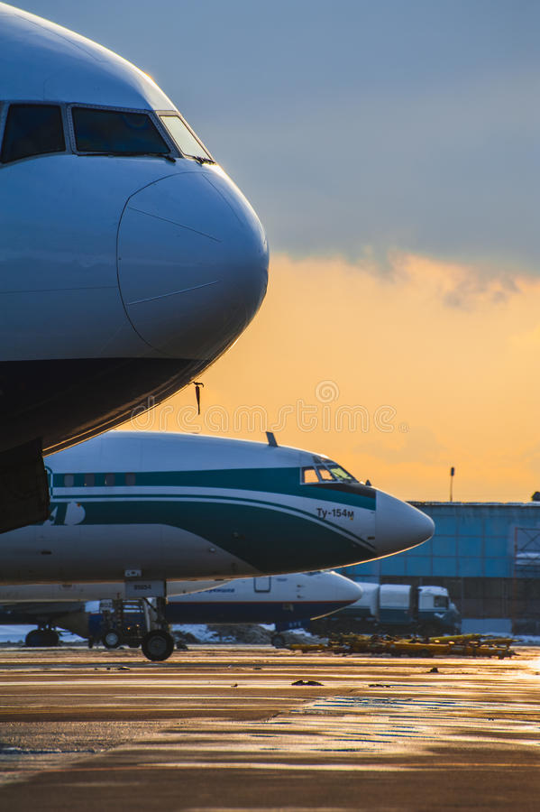 Vliegtuigenparkeren bij de luchthaven bij zonsondergang royalty-vrije stock foto's