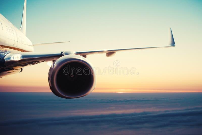 Vliegtuigenvlucht over de wolken tijdens zonsopgang stock fotografie