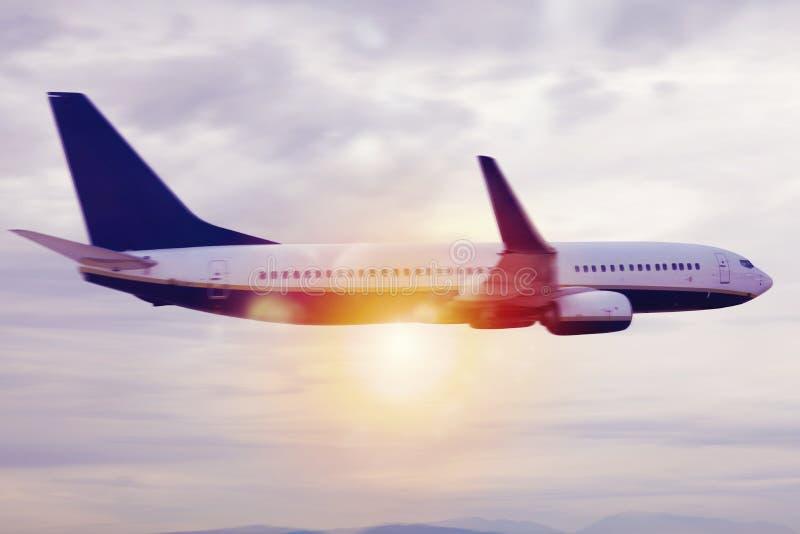 Vliegtuigenvlucht over de wolken tijdens zonsopgang stock afbeelding