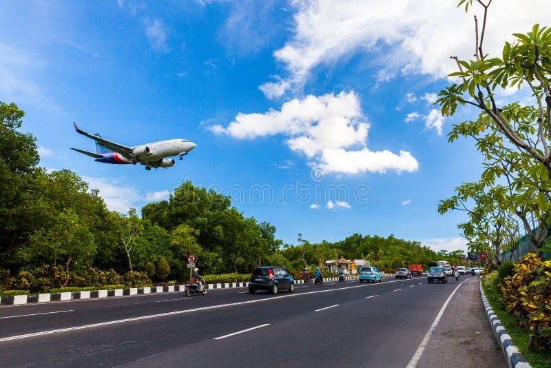 Vliegtuiggevaar die dichtbij weg op het tropische eiland Bali, de Luchthaven van Ngurah Rai, Tuban, Badung-Regentaat, Bali, Indon stock fotografie