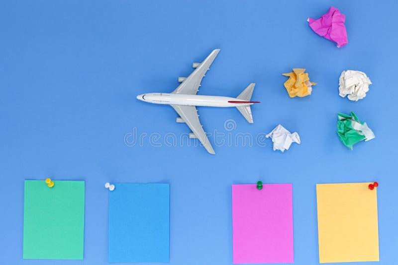 Vliegtuigmodel met kleurrijke lege document nota over blauwe achtergrond royalty-vrije stock foto