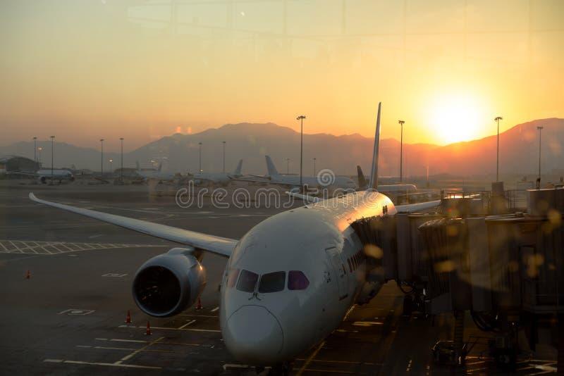 Vliegtuigparkeren bij Hong Kong International-luchthaven in zonsopgang stock foto's