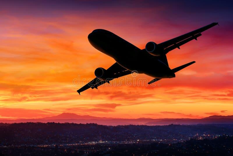 Vliegtuigsilhouet in de hemel bij zonsondergang stock fotografie