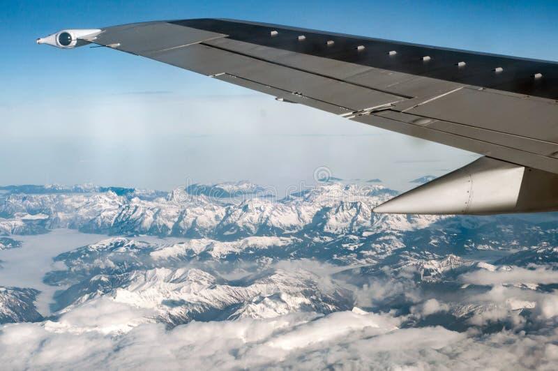 Vliegtuigvleugel die boven sneeuwbergen vliegen royalty-vrije stock afbeeldingen