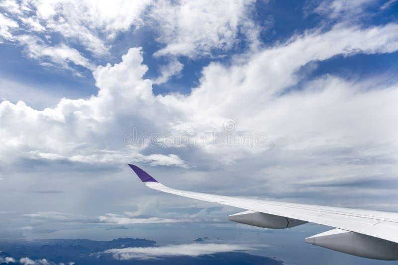 Vliegtuigvleugel die over witte wolken vliegen royalty-vrije stock afbeelding