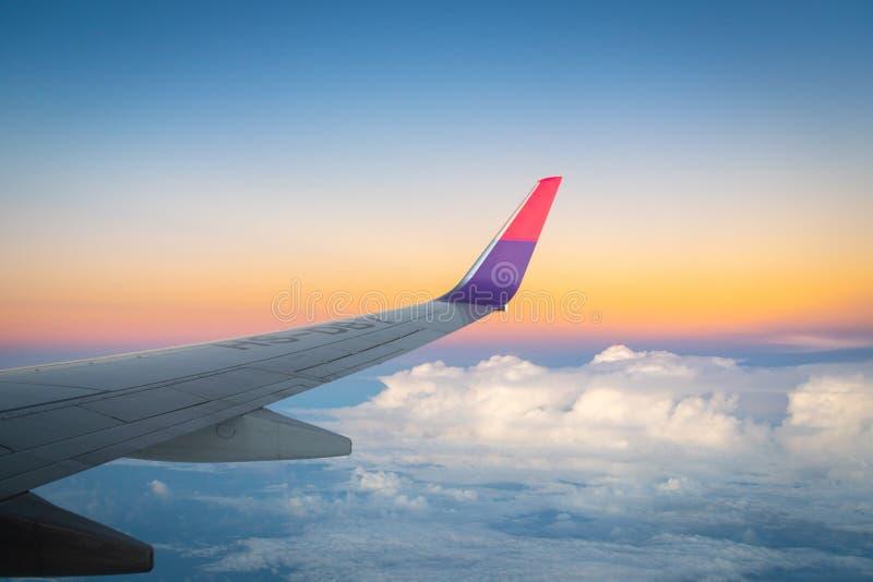Vliegtuigvleugel tijdens de vlucht van venster, zonsonderganghemel, schemeringhemel stock fotografie
