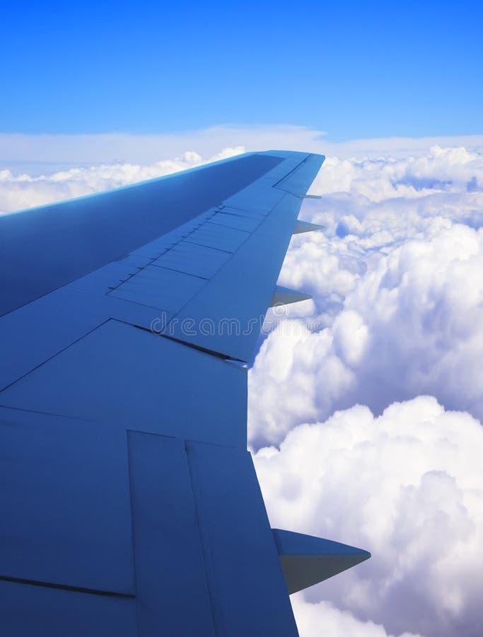 Vliegtuigvleugel zoals die van venster wordt bekeken die wolken en blauwe hemel tonen royalty-vrije stock afbeelding