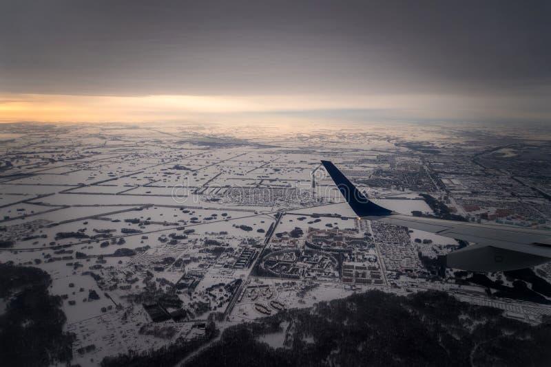 vliegtuigvliegen over een kleine stad dichtbij het bos in de winter tijdens zonsondergang in de avond royalty-vrije stock foto