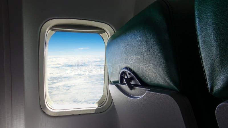 Vliegtuigzetel en vensters binnen een vliegtuig De passagiersvenster van het wolkenvliegtuig stock afbeelding