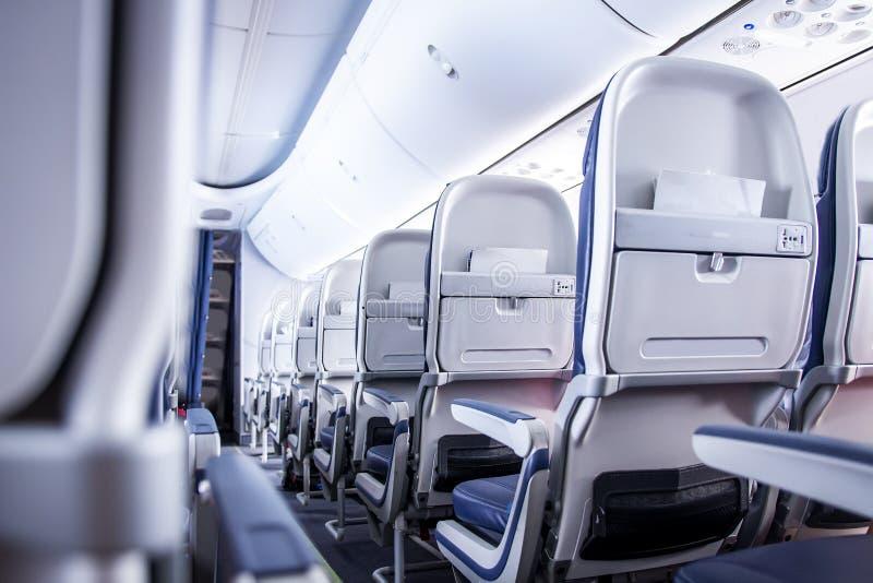 Vliegtuigzetels in cabine Commerciële vliegtuigencabine met rijen van zetels onderaan de doorgang Uit de toeristenklasse stock fotografie