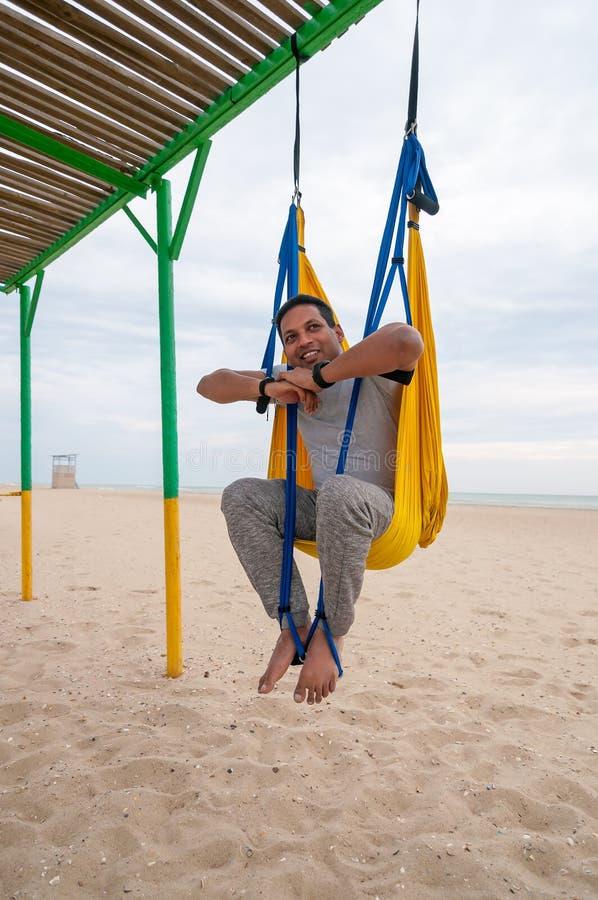 Vliegyoga, mens die yogaoefeningen op de overzeese achtergrond doen Sport en gezond concept stock foto's