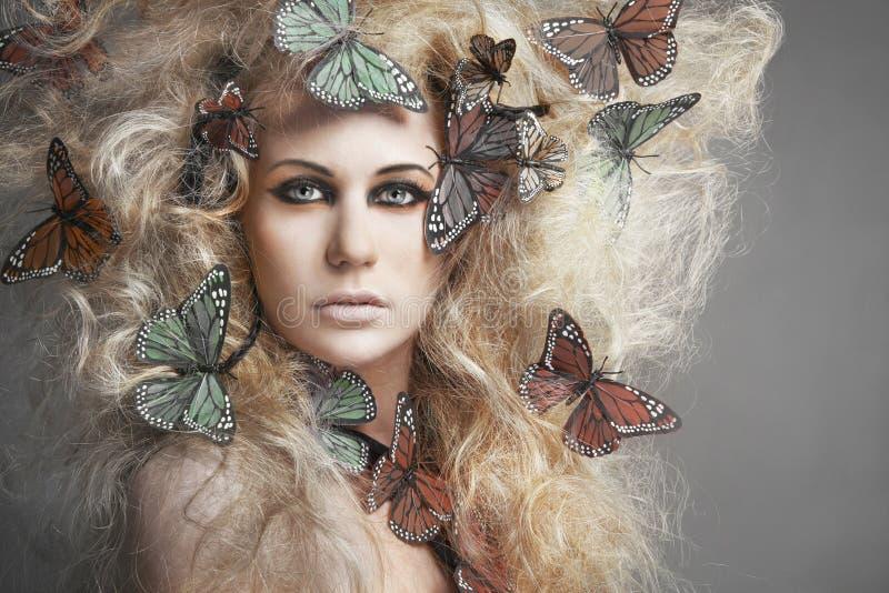 Vlinder in krullend blond haar. stock fotografie
