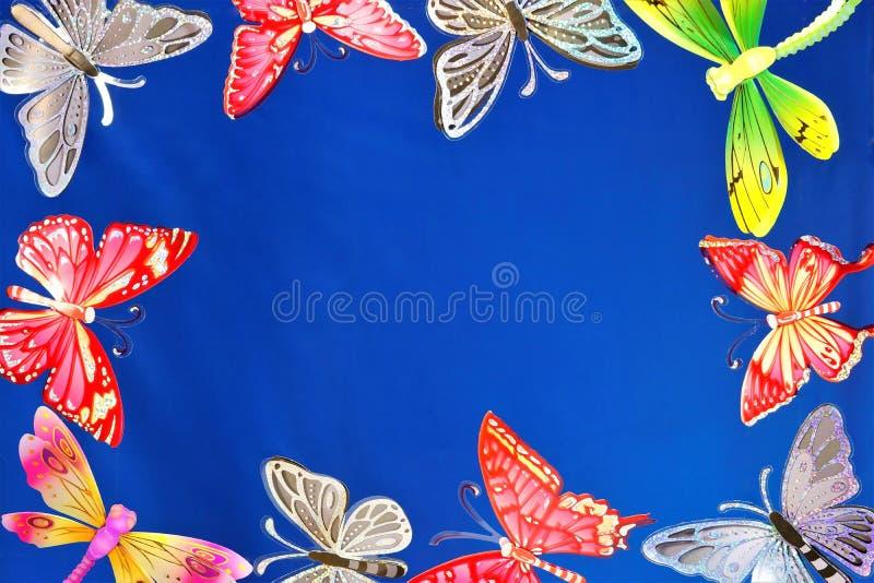 Vlinders en libellenkader voor ontwerp, op blauwe hemelachtergrond royalty-vrije stock afbeelding