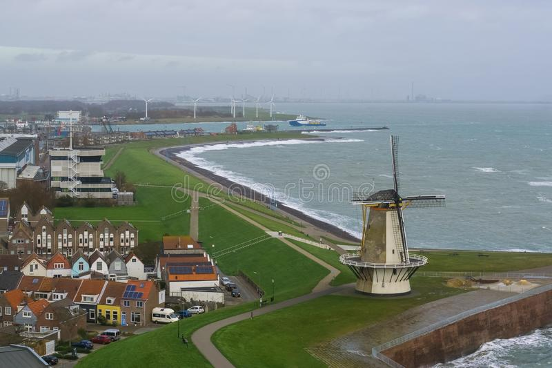 vlissingen和看法,典型的荷兰风景,普遍的城市风车的美好的地平线与有些房子的海上的在西兰省 库存照片