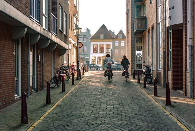 Vlissingen Nederländerna - April 2015: Gatasikt med att cykla för moderna byggnader för röd tegelsten och för två damer arkivfoton