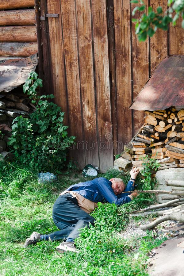 Vlkolinec, Slovakia, 13th. August, 2010 : Man sleeping on grass stock photography