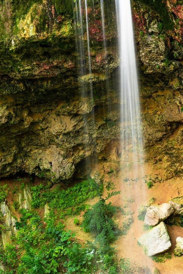 Vloeiende waterval in het bos op de berg stock fotografie