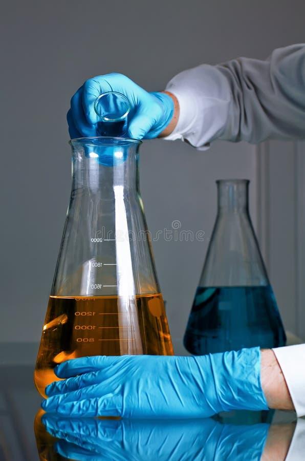 Vloeistof die zich in een fles mengt stock foto's