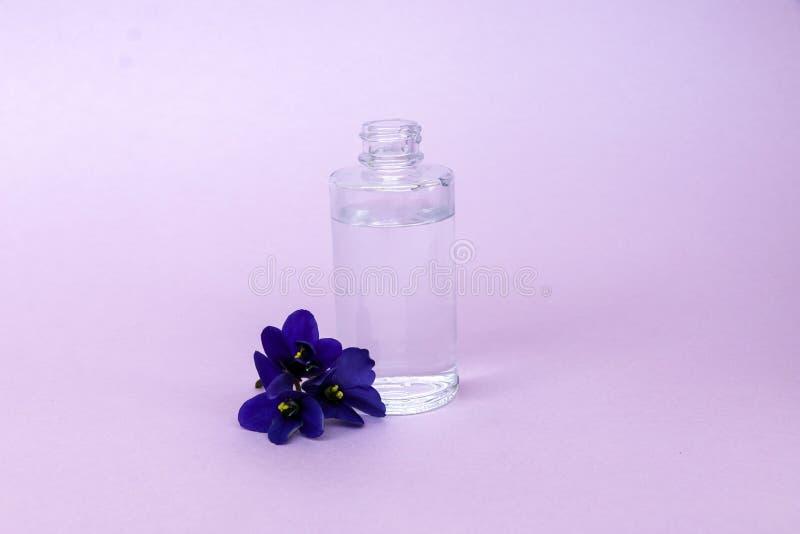 Vloeistof in transparante fles met pipet voor stijgende elektronische sigaretten met geur en smaak van bloemen, op roze achtergro stock afbeeldingen