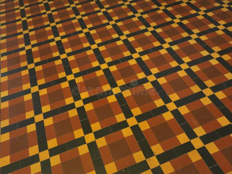 Vloer met patroon in rode, gele en zwarte tegels stock afbeeldingen