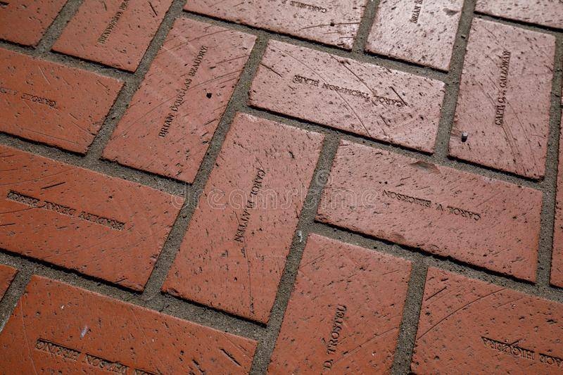 Vloer rode bakstenen met gravurenamen bij het Vierkant van het Pioniersgerechtsgebouw in Portland royalty-vrije stock foto's