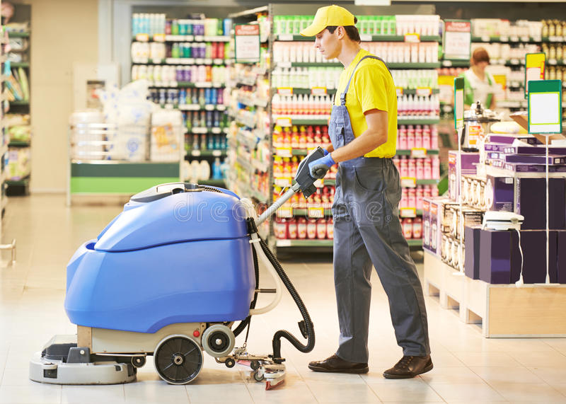 Vloer van de arbeiders de schoonmakende opslag met machine