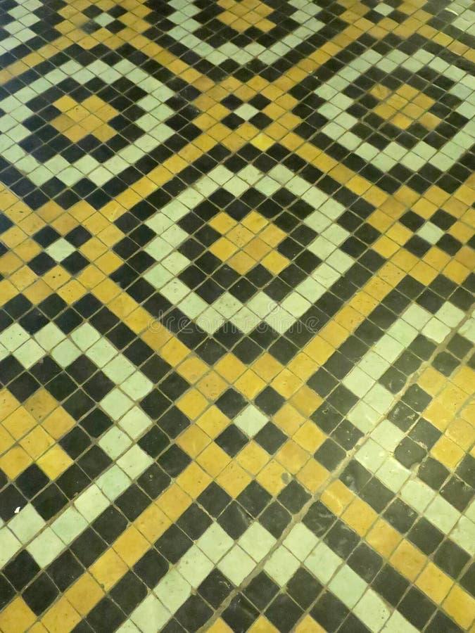 Vloer van gele zwart-witte tegels die een bewegend patroon vormen royalty-vrije stock foto
