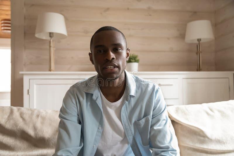 Vlog di registrazione del giovane tipo africano a casa che esamina webcam fotografia stock libera da diritti