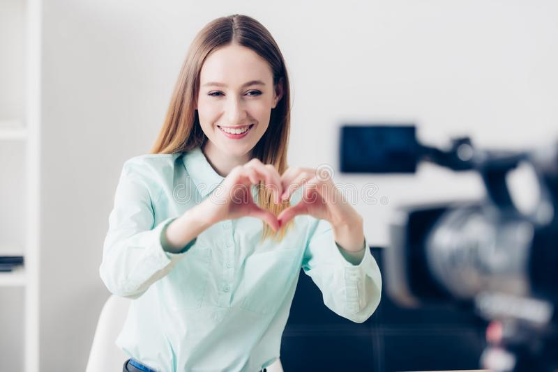 Vlog di video blogger femminile attraente felice e cuore di registrazione di mostra con le dita fotografia stock