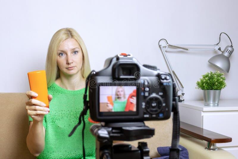 Vlog ou podcast visuel femelle d'enregistrement de blogger, coulant en ligne Appareil-photo brouillé sur le trépied dans l'avant image libre de droits