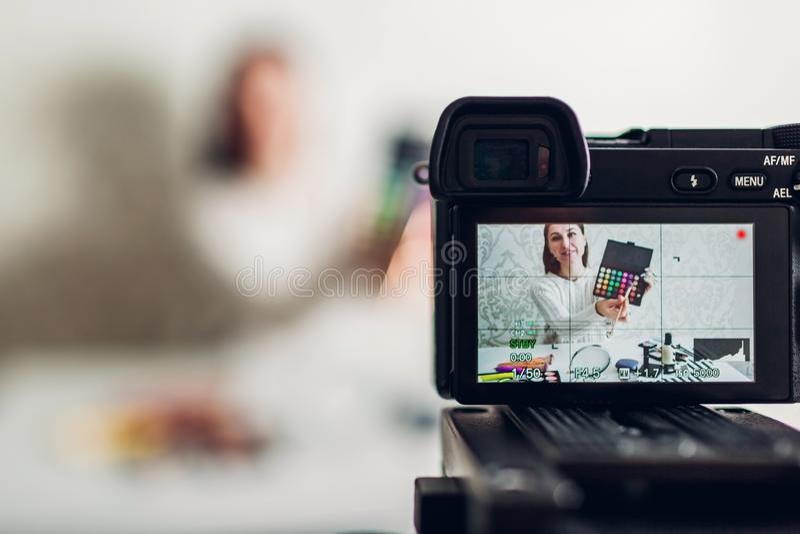 Vlogger красоты молодой женщины профессиональные или запись блоггера составляют консультационное используя камеру и треногу стоковое изображение rf
