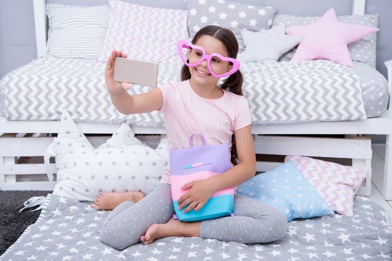 Vlogger bonito que flui o vídeo A criança da menina senta-se na cama em seu quarto e em tomar o selfie ou em fluir o vídeo A cria foto de stock