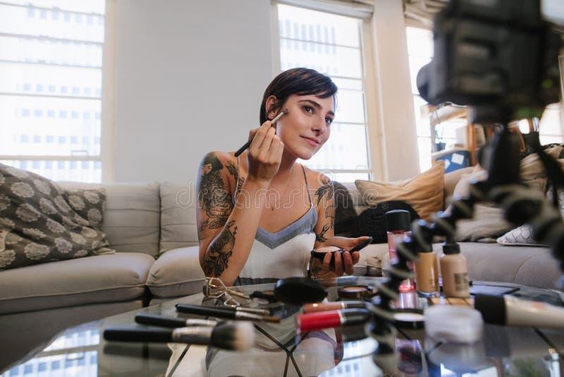 Vlogger de la belleza que hace un tutorial video en maquillaje fotos de archivo