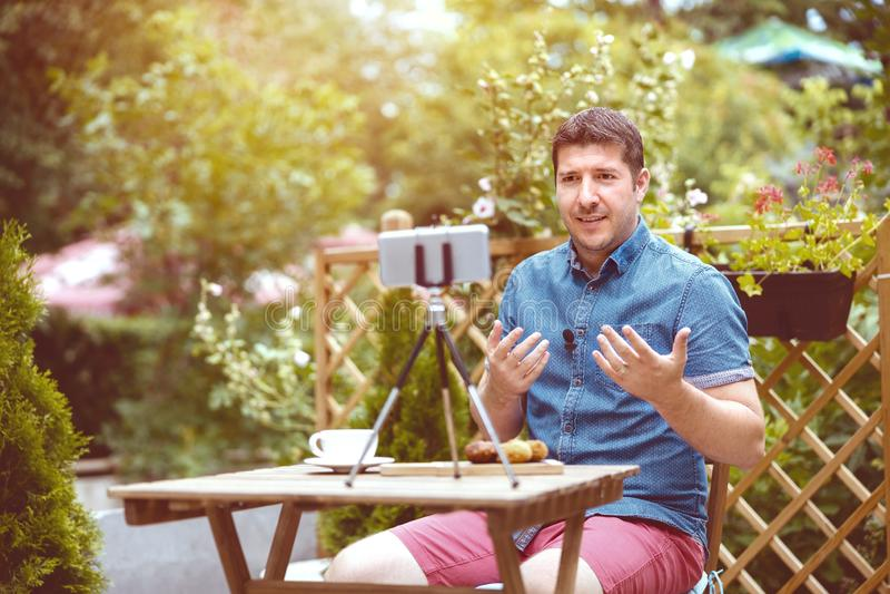 Vlogger do homem usando o telefone esperto ao gravar o vídeo para o vlog da alimentação, nômadas de Digitas que compartilha do ín fotografia de stock